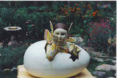 A restored Sergio Bustamante butterfly girl emerging from a monumentally sized egg.