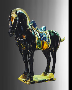 A restored Tang Dynasty funerary horse that is black, and the saddle is glazed in blue, green, and cream colors. The horse is monumental 